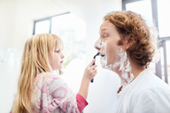 Daughter helping father shave face in bathroom - CAIF09384