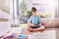 Boy with digital tablet assembling jigsaw puzzle on sunny living room floor - CAIF09387