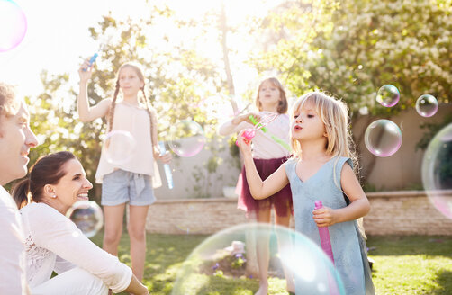 Parents watching daughters blowing bubbles in sunny back yard - CAIF09393