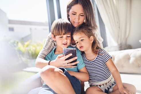 Mother and children using cell phone in sunny living room - CAIF09396