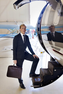 Portrait of businessman standing on staircase of airplane - CAVF04557