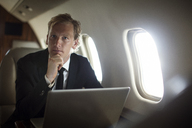 Portrait of confident businessman sitting with laptop in airplane - CAVF04560