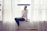 Woman using mobile phone while sitting on window at home - CAVF04671