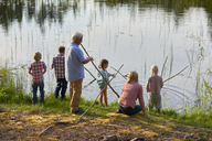 Grandparents and grandchildren fishing at lakeside - CAIF09423