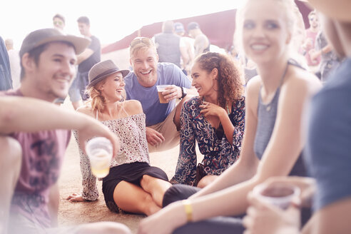 Young friends hanging out drinking beer and talking at music festival - CAIF09444