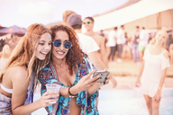 Young women posing for selfie at music festival - CAIF09447