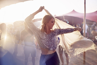 Young woman dancing with scarf at music festival - CAIF09453