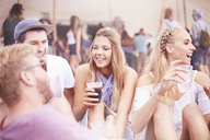 Young friends hanging out drinking at music festival - CAIF09456