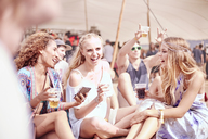 Young women hanging out drinking at sunny music festival - CAIF09459