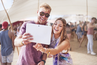 Young couple taking selfie with digital tablet at music festival - CAIF09462