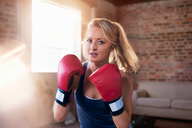 Portrait tough young woman boxing in studio - CAIF09513