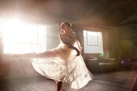 Graceful female dancer dancing in sunny studio - CAIF09519