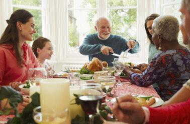 Multi-ethnic family enjoying Christmas dinner table - CAIF09531