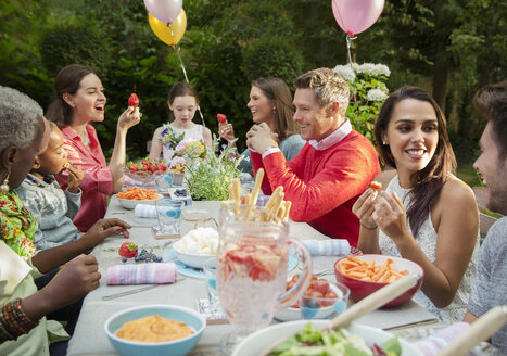 Family and friends enjoying birthday garden party at patio table - CAIF09534