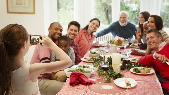 Girl with camera phone photographing multi-ethnic family at Christmas dinner table - CAIF09537