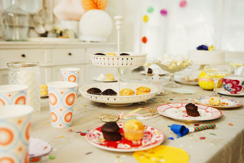 Cupcakes and decorations on birthday party table - CAIF09540