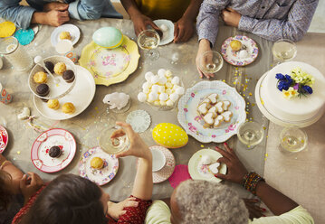 Overhead view family enjoying Easter desserts and drinking champagne at table - CAIF09543