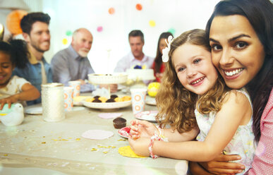 Portrait smiling mother and daughter hugging at birthday party table - CAIF09546