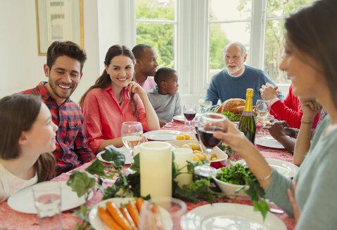 Multi-ethnic multi-generation family enjoying Christmas dinner at table - CAIF09552
