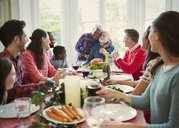 Affectionate multi-ethnic senior couple hugging at family Christmas dinner table - CAIF09564