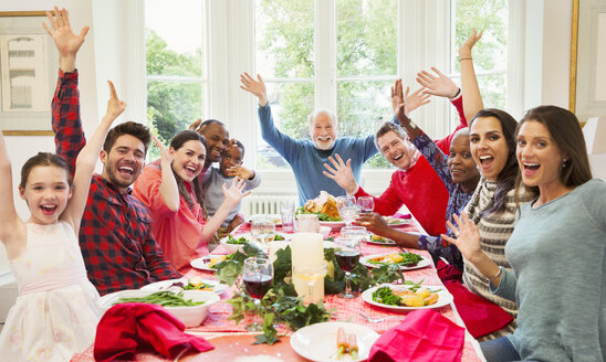 Portrait enthusiastic multi-ethnic multi-generation family waving at Christmas dinner table - CAIF09567