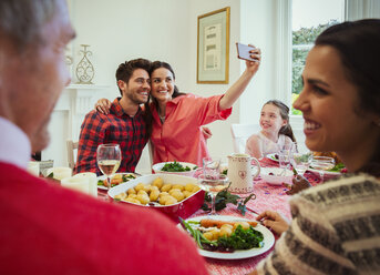 Couple with camera phone taking selfie at Christmas dinner table - CAIF09570