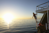 Man leaning on summer houseboat railing over sunset ocean - CAIF09576