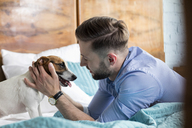 Man petting Jack Russell Terrier on bed - CAIF09693