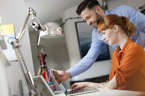Business people using laptop in office - CAIF09702