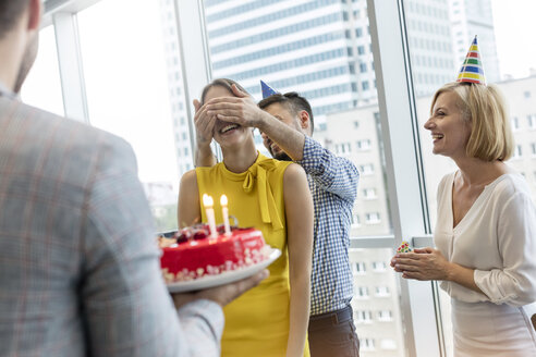 Business people celebrating birthday with cake in office - CAIF09750