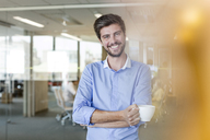 Portrait confident businessman drinking coffee in office - CAIF09753