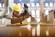 Steel worker using large wrench in factory - CAIF09771