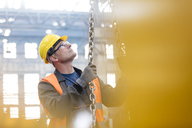 Steel worker holding chain in factory - CAIF09774
