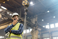 Steel worker with walkie-talkie in factory - CAIF09780