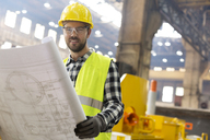 Portrait smiling engineer with blueprints ins steel factory - CAIF09783