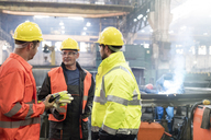 Steel workers talking in factory - CAIF09789