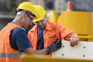 Workers examining part in factory - CAIF09798