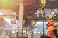 Steel workers operating crane in factory - CAIF09804
