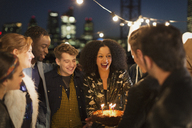 Young friends celebrating birthday at rooftop party - CAIF09819
