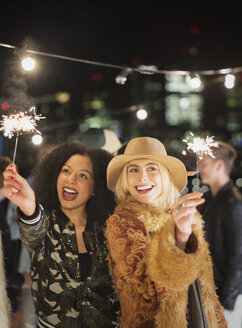Young women waving sparklers at rooftop party - CAIF09825
