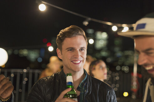 Smiling young man drinking beer at rooftop party - CAIF09828