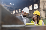 Manager and female steel worker meeting in factory - CAIF09837
