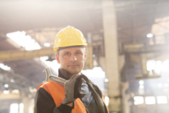 Portrait confident steel worker holding large wrench in factory - CAIF09867