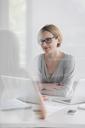Portrait confident businesswoman working at laptop - CAIF09936