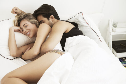 Happy couple lying on bed at home - CAVF04886