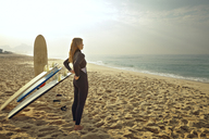 Woman putting on wetsuit while standing by surfboards at beach - CAVF04919