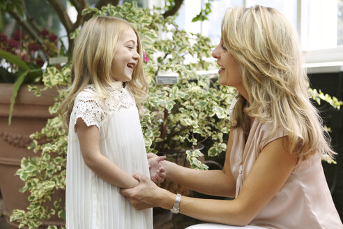 Happy mother holding hands while talking to daughter - CAVF04997