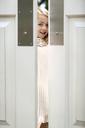 Portrait of happy girl looking through door - CAVF05000