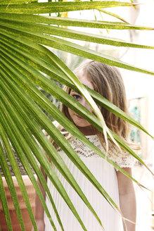 Portrait of girl looking through leaves - CAVF05009