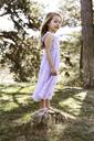 Happy girl standing on rock in backyard - CAVF05012